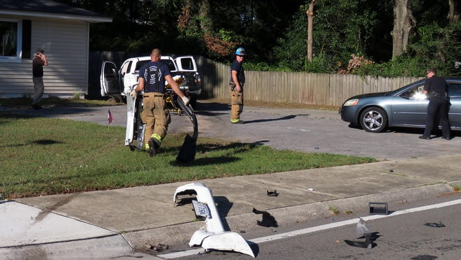 Pensacola city firefighters and police officers responded to the scene of a accident at 900 E. Cross Street and 9th Avenue late Sunday afternoon. To clear the roadway of debris a firefighter is shown picking up pieces of a pickup truck that appeared to narrowly miss the house in the background while a police officer talks to the driver of another vehicle.