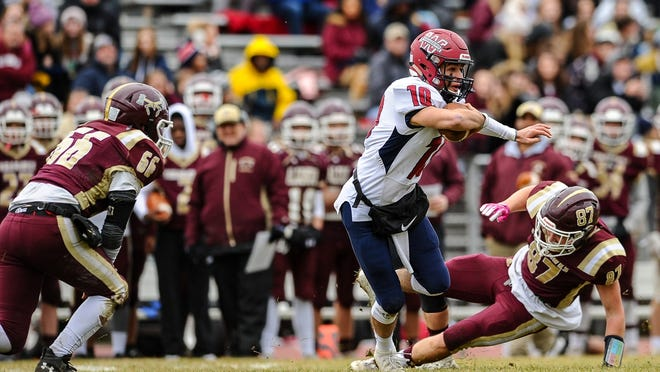 Former Westborough High quarterback Luke Lentine sidesteps Algonquin's Colin Wing (right) on Thanksgiving Day of last year. Lentine recently received a plaque for being named a Joseph R. Mewhiney Central Massachusetts Chapter Football Scholar-Athlete.