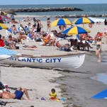In this photo taken June 23, 2014, beachgoers enjoy the sand in Atlantic City. A preliminary report released on Tuesday by two emergency managers hired by New Jersey Gov. Chris Christie to help turn around Atlantic City's struggling finances recommended layoffs and spending cuts.