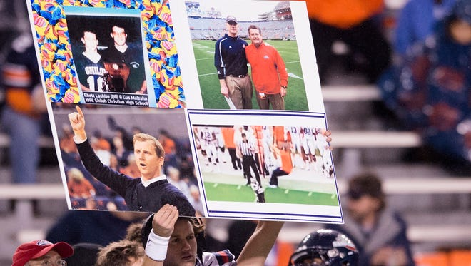 Samford quarterback Albert Mitchell (4) holds up a play card with Rhett Lashlee photographs during the NCAA football game on Saturday, Nov. 22, 2014, at Jordan-Hare Stadium in Auburn, Ala.