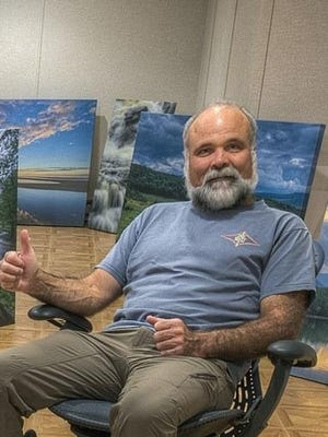 Hardie Truesdale in front of his photographs.