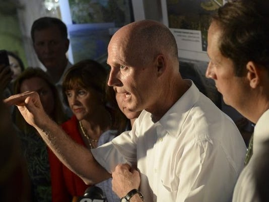 Photo by Deborah Silver FILE PHOTO Gov. Rick Scott addresses questions during a news conference held at the St. Lucie Lock and Dam Visitor's Center in Stuart in August. Scott is flanked by state Rep. Gayle Harrell, R-Stuart (left), and Sen. Joe Negron, R-Stuart (right).