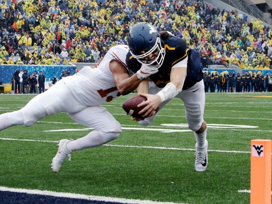 Texas defensive back Brandon Jones (19) tackles West Virginia quarterback Will Grier (7) short of the goal line during the first half of an NCAA college football game, Saturday, Nov. 18, 2017, in Morgantown, W.Va. Grier injured his hand in during the play and left the game. (AP Photo/Raymond Thompson)