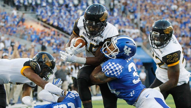 Southern Mississippi running back Ito Smith scores a touchdown after slipping past Kentucky linebacker Jordan Jones, right, in the first half of an NCAA college football game Saturday, Sept. 3, 2016, in Lexington, Ky. (AP Photo/David Stephenson)