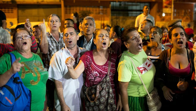 Pro-government supporters demand that a polling station reopen, after its official closing, during congressional elections in Caracas, Venezuela, Dec. 6, 2015.