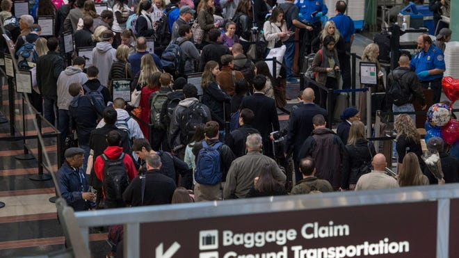 Travelers line up at a Transportation Security Administration checkpoint at Reagan National Airport on Nov. 26, 2013.