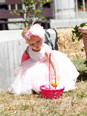 Danica Moffett, 1, places an egg she found into her basket, during an Easter egg hunt at a past Spring Carnival at the Ventura County Fairgrounds.