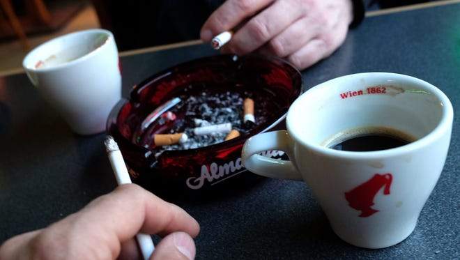 Guests of a Vienna's Cafe/Bar smoke cigarettes with their drinks in Vienna, Austria, on March 22, 2018.