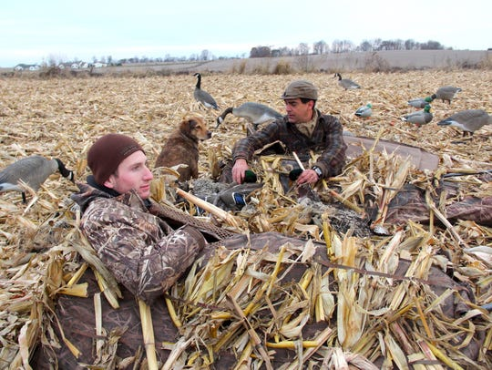 Bryan Muche, right, accepts a drake mallard retrieved