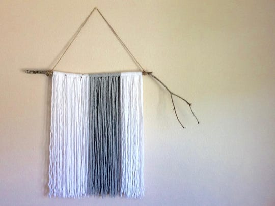 Yarn and a tree branch come together easily to make this wall hanging. Mix it up with different color yarn or trim the yarn at the end to be different lengths or diagonal in appearance.