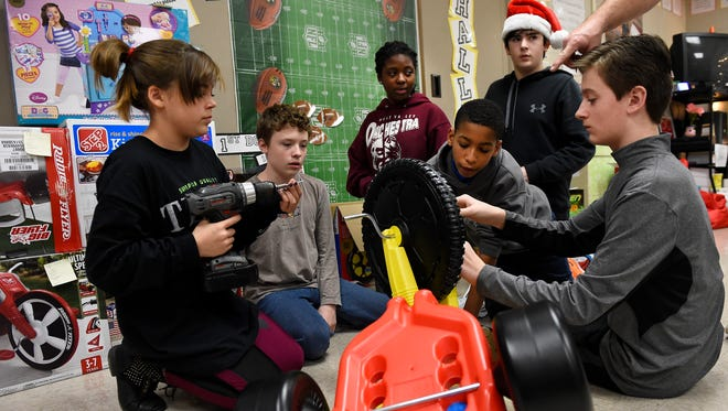West Valley Middle School students, left to right, Jourdan Rouse, Grant Burgess, McKenna Cook, Kenneth Parker-Smith, Jack Saunders and Jake Greene, construct toys to be donated to the Mission of Hope nonprofit in Amy Crawford's seventh grade class on Dec. 9, 2014. The students raised funds to purchase the toys for children.