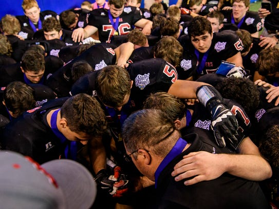 The Southridge Raiders pray together after winning