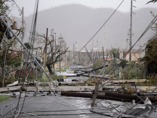 Electricity poles and lines lay toppled on the road