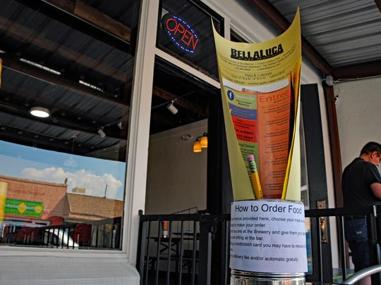 Menus from nearby restaurants await customers on tables at T or C's downtown brewery. Several eateries deliver food to the brewery.