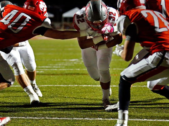 Nixa High School running back Nicos Oropeza (32) runs in between Tiger defenders for a touchdown during first quarter action of the game between Nixa High School and Ozark High School held at Tiger Stadium in Ozark, Mo. on Oct. 7, 2016.