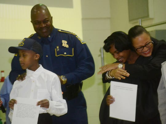 "Judge Monique Rauls (back, right) hugs Julius Patrick Elementary School student Leola Stevenson (front, right) who portrayed her in a portion of the school's black history program entitled ""Alexandria Museum of African-American History"" on Friday. Louisiana State Police Troop E commander Capt. Jay D. Oliphant Jr. (back, second from left) stand with Julius Patrick Elementary student Antonio Dearbone (front, left), who portrayed him in the program."