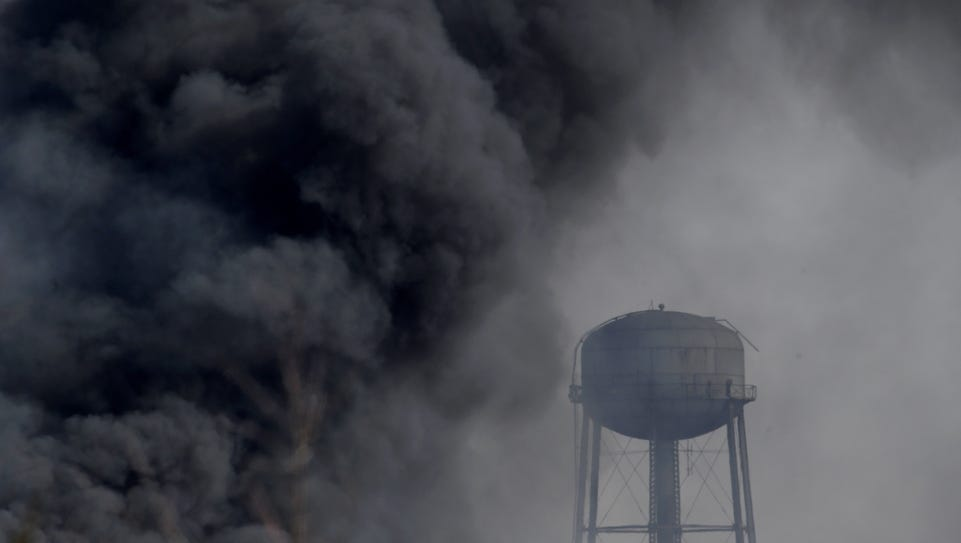 Smoke rises near a water tower at the site of a large