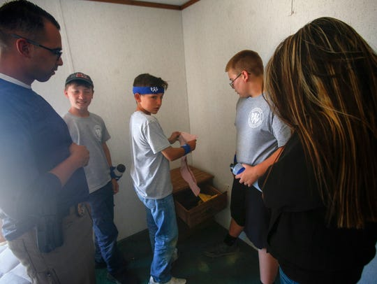 Junior Law Enforcement Academy participant Jesse Gomez, center, locates potential evidence in a simulated homicide investigation Thursday at Safety City in Kirtland.