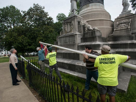 Workers remove the Confederate flags from outside the