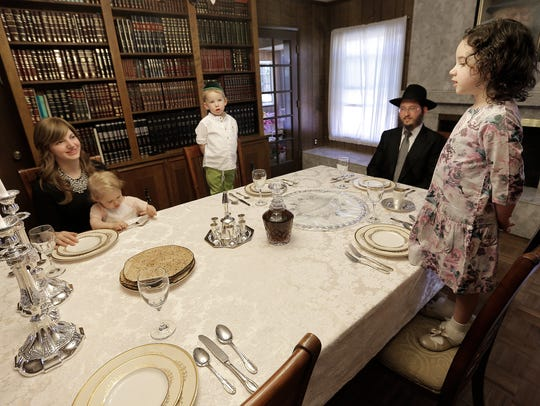 The Greenberg family listens as Musia Greenberg, 4,
