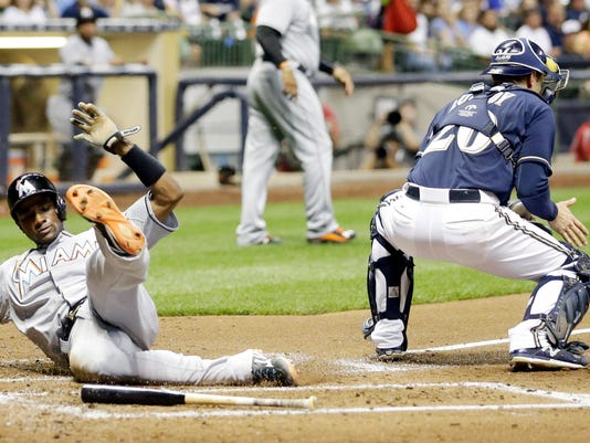 Miami Marlins' Adeiny Hechavarria scores past Milwaukee Brewers catcher Jonathan Lucroy during the third inning of a baseball game Monday, Aug. 17, 2015, in Milwaukee. Hechavarria scored from second on a hit by Dee Gordon. (AP Photo/Morry Gash)