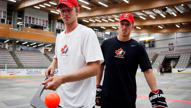 Team Canada's Eric Staal, left, and brother Marc Staal take part in a floor hockey game at the Canadian orientation camp in Calgary.