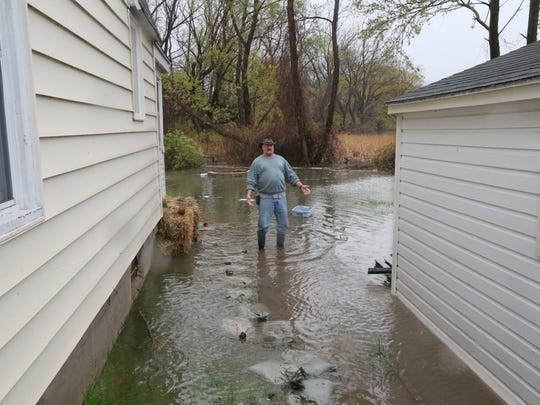 """Tim Berdych, with Christian Brothers Concrete Construction Company of Rochester, at work on a flooded home at 565 Edgemere Drive in Greece on May 5, 2017. """"There's a sidewalk under here someplace,"""" he said."""