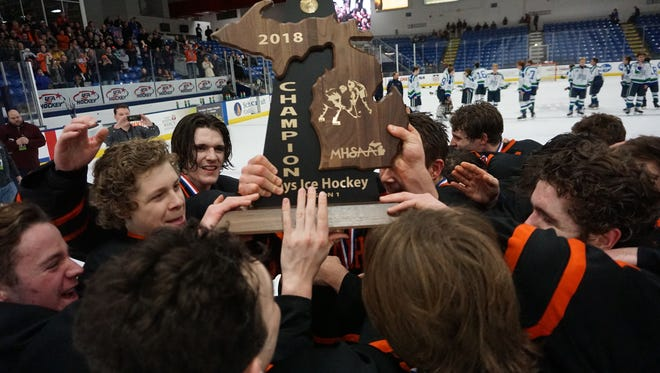 Brighton players hoist the 2018 state Division 1 hockey championship trophy following a 5-2 victory over Saginaw Heritage on Saturday, March 10 at USA Arena in Plymouth.