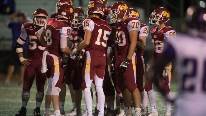 The Lobos huddle up before a play in a game against Arvada West at French Field Thursday, October 20, 2016.