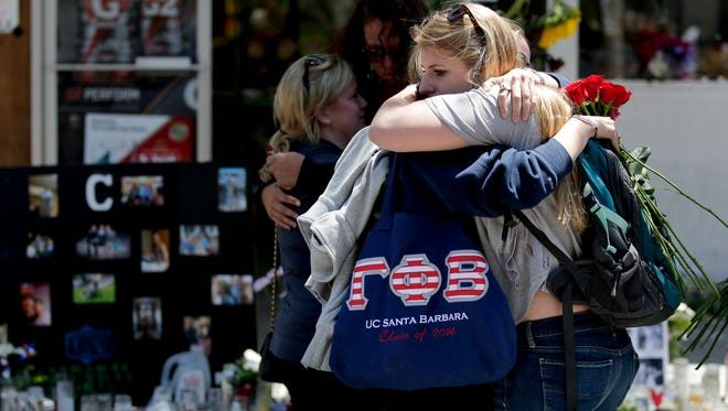 Mourners hug in front of the IV Deli Mart, where part of the mass shooting took place, on, May 27, 2014, in the Isla Vista area near Goleta, Calif.