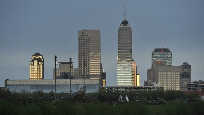 The low sun reflects off the downtown Indianapolis skyline looking down the White River from New York Street.