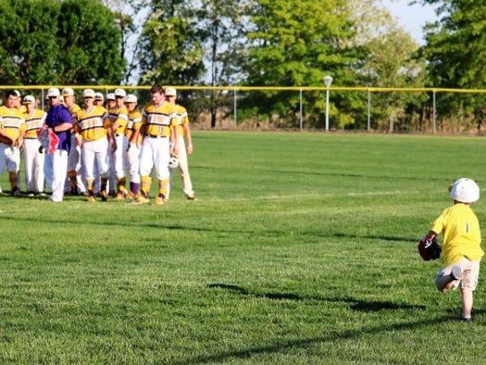 Michael Grzankowski runs onto the field to join his