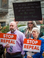 Signs are held during a rally asking Sen. Lamar Alexander to stop his rush to repeal the Affordable Care Act held outside his office in downtown Knoxville on Thursday, Jan. 19, 2017.