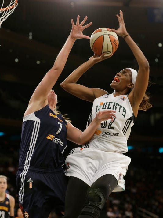 FILE - In this Aug. 8, 2014, file photo, New York Liberty's Swin Cash looks for a shot over Connecticut Sun's Kayla Pedersen during a WNBA basketball game in New York. Cash, who is retiring after the season, is to be honored after the Liberty's game Wednesday night, Sept. 7, in New York. (AP Photo/Frank Franklin II, File)