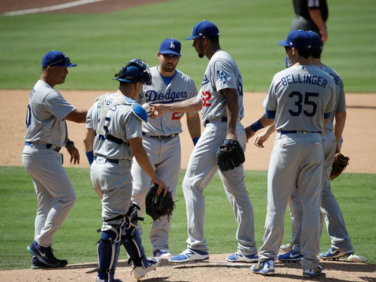 FILE - In this Sept. 2, 2017, file photo, Los Angeles Dodgers relief pitcher Wilmer Font, center, hands the ball to manager Dave Roberts as he is relieved during the sixth inning of a baseball game against the San Diego Padres, in San Diego. No need for catchers to worry about getting they're running in, especially during the postseason. They are taking so many trips to the mound for discussions, the average time of a nine-inning game is 3 hours, 32 minutes during the postseason, up 18 minutes since 2015. (AP Photo/Jae C. Hong, File)