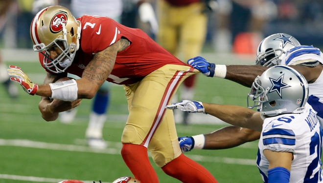 San Francisco 49ers quarterback Colin Kaepernick (7) fights for extra yardage on a short run as Dallas Cowboys defensive back Sterling Moore (26) and a teammate attempt the stop in the first half of an NFL football game, Sunday, Sept. 7, 2014, in Arlington, Texas. (AP Photo/LM Otero)