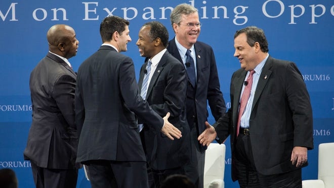 Republican presidential candidates Ben Carson, center, Jeb Bush and New Jersey Gov. Chris Christie, right, shake hands with Sen. Tim Scott, R-S.C., left, and House Speaker Paul Ryan of Wis. at an economic forum  in Columbia, S.C.  The candidates said their party must do more to convince poor Americans that conservative policies and not an active federal government, will expand economic opportunity.   (AP Photo/Sean Rayford)