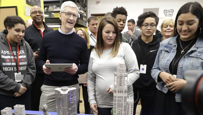 Apple CEO Tim Cook uses the Swift Playgrounds App on the new 9.7-inch iPad to maneuver a ball, bottom right, at an Apple educational event at Lane Technical College Prep High School March 27, 2018, in Chicago.