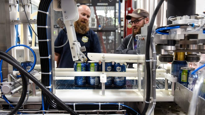 Cans are filled with beer on the canning line Wednesday, May 24 on the first day of production at the new Beaver Island Brewing Co. facility in St. Cloud.