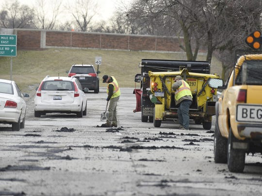 Brandon Jerard, left, and Bruce Ball of the Royal Oak highway division prepare to lay tar on potholes on northbound Stephenson Hwy. **Pot holes repairs on I-696 westbound at I-75, and the northbound Stephenson Hwy service drive this morning., February 22, 2018, Detroit, Mi. (Clarence Tabb Jr./The Detroit News)