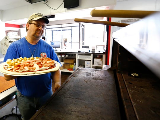 Owner Sean Zyduck opens an oven to cook a pizza he