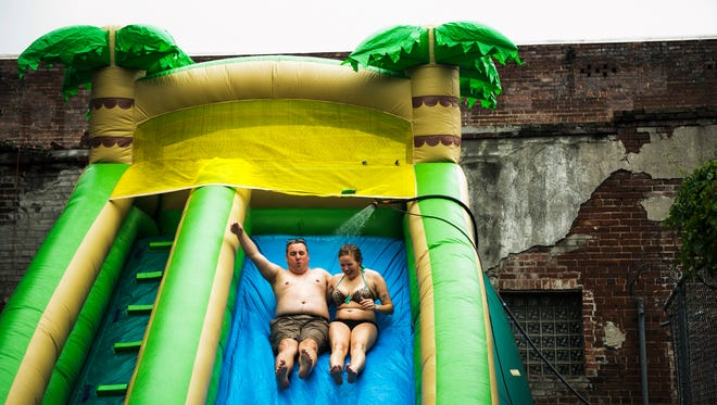 June 4, 2017 - Water showers Michael Zepatos, 30, and Dallas Hall, 24, as they take a trip down a water slide during the Sache Sunday Block Party at 525 S. Main St. on Sunday. The event was held to benefit the Memphis Food Bank.