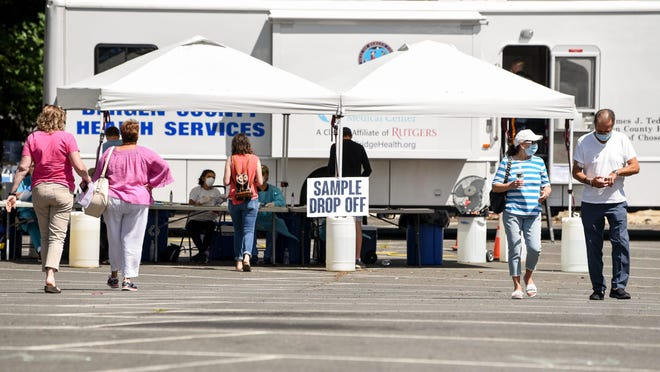 People drop off saliva samples at the sample tent at a Covid-19 testing center in Ramsey on Wednesday July 1, 2020. This testing center offers the saliva test as opposed to the nasal swab test.