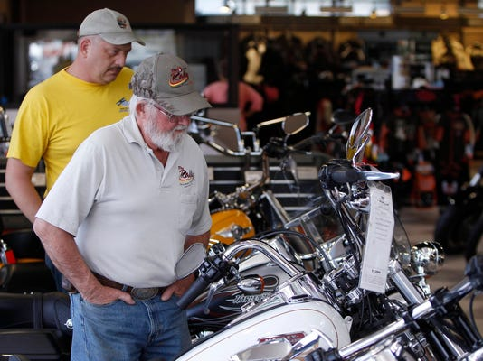 Customers look at the showroom inventory at Harley-Davidson of Frederick in Frederick, Md. in this October 23, 2012 photo. Unless the Milwaukee-based company began to attract younger riders and penetrate new markets, analysts warned the waning of its overwhelmingly white, male and middle-aged base would hurt sales in North America, where it still earns two-thirds of its revenue. (REUTERS/Gary Cameron/Files)