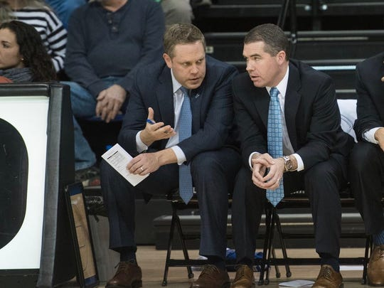 Former UNC-Asheville assistant Wes Long (left) chats with former Bulldogs coach Nick McDevitt (right) during a game in the 2017-18 season. Long and McDevitt have since taken up the same positions at MTSU.