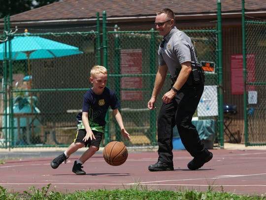 Jayce Dailey, 8, plays basketball with Cpl. Eric Biehl