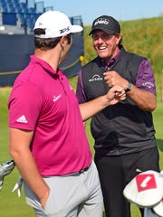 Jon Rahm (left) and Phil Mickelson fist bump during