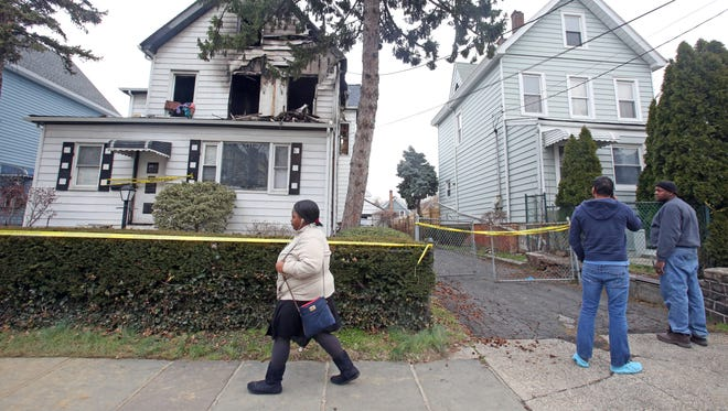 People walk pass a home in Mount Vernon on Feb. 27, 2017, that caught fire early Sunday and left two people dead.