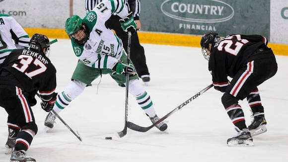 North Dakota's Michael Parks tries to control the puck as St. Cloud State's Joey Rehkamp (37) and Nick Oliver (27) try to get to the puck during the first period of the Nov. 21 game at the Herb Brooks National Hockey Center in St. Cloud.