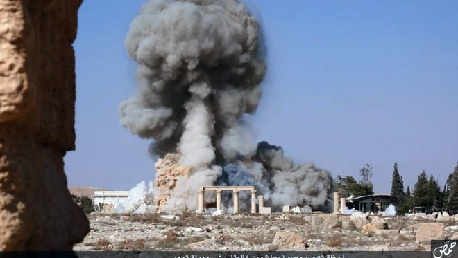 This undated photo released Aug. 25, 2015, on a social media site used by Islamic State militants, which has been verified and is consistent with other AP reporting, shows smoke from the detonation of the 2,000-year-old temple of Baalshamin in Syria's ancient caravan city of Palmyra.